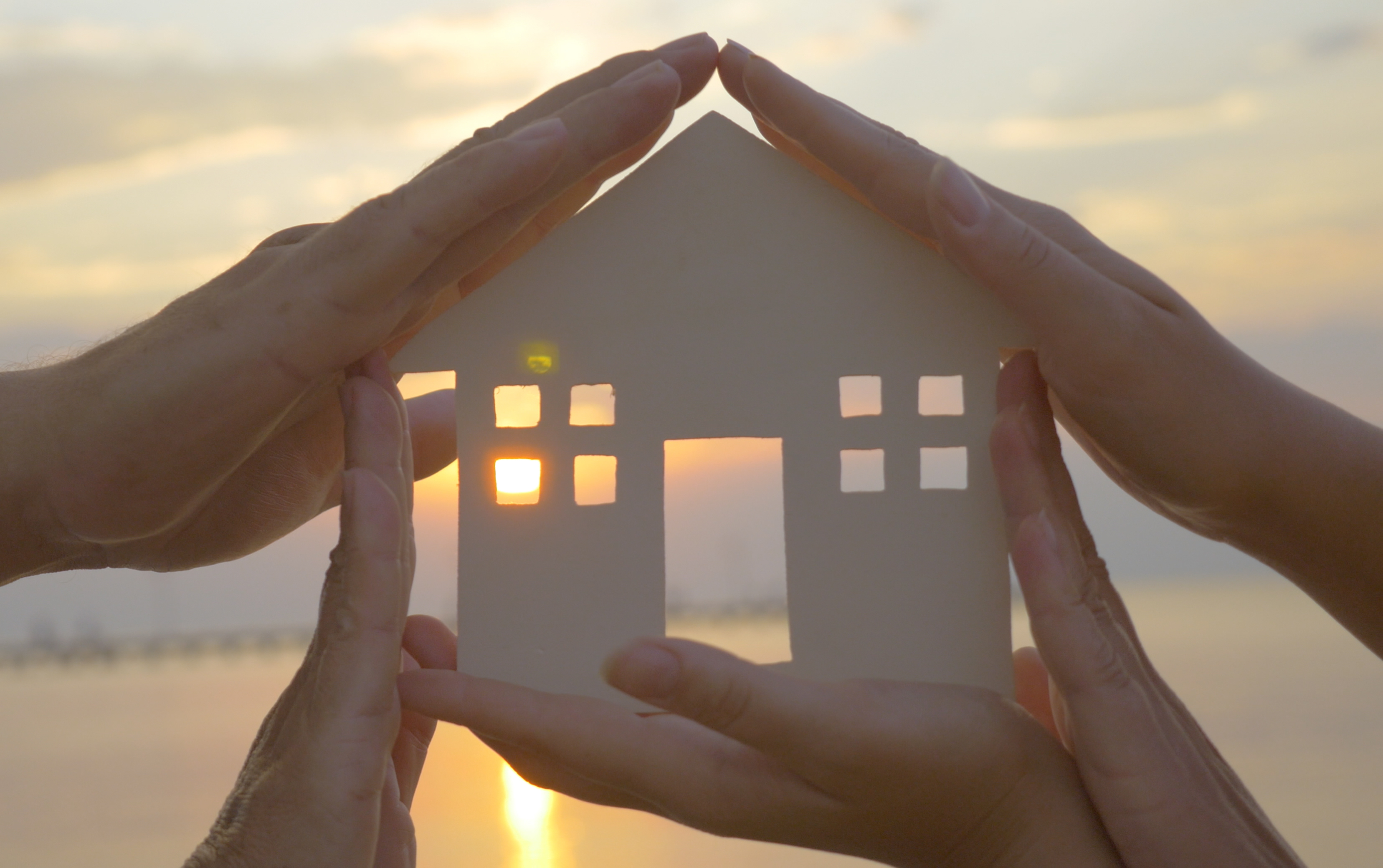 Hands holding small house cutout