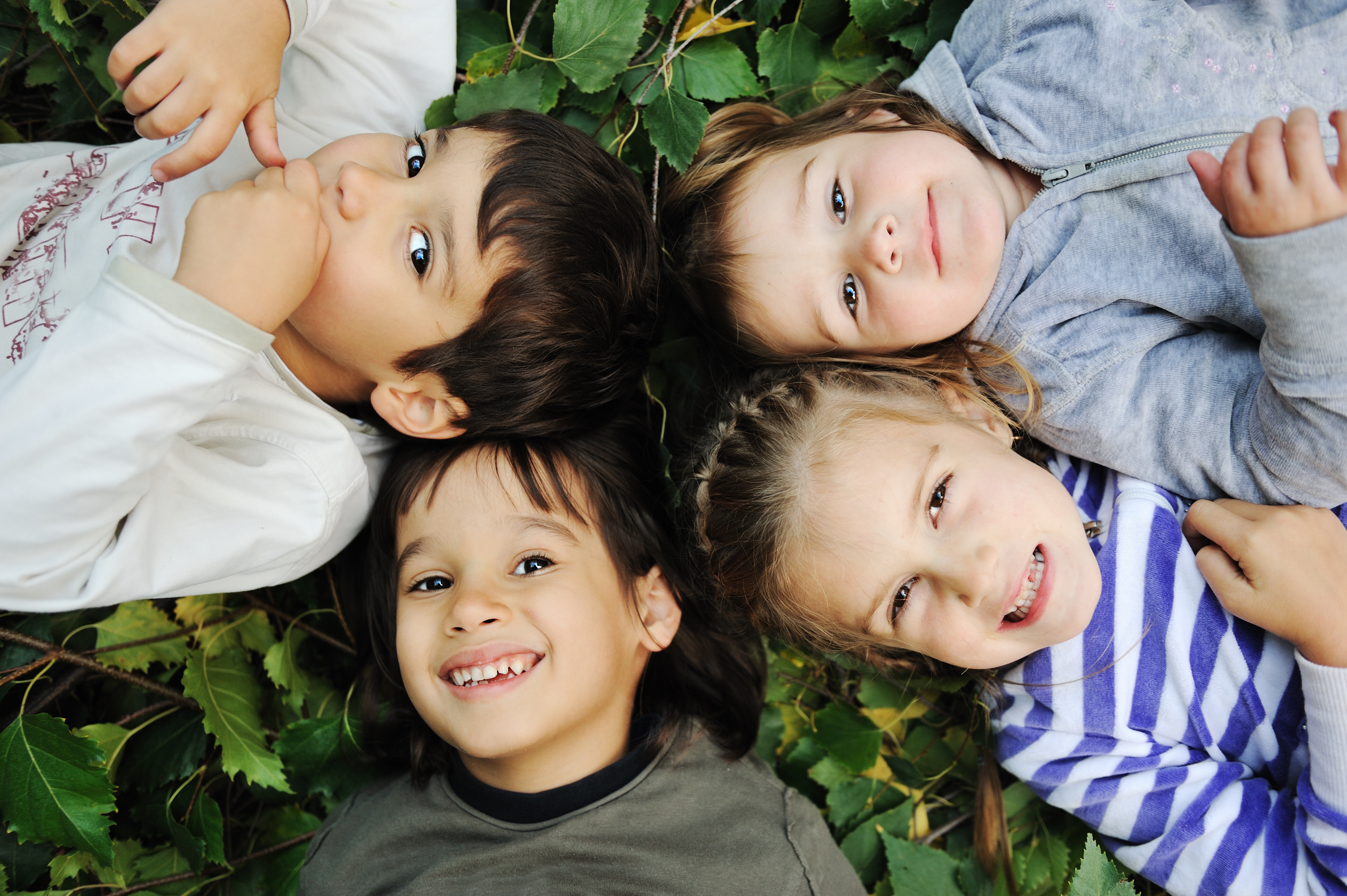 kids smiling laying on the grass